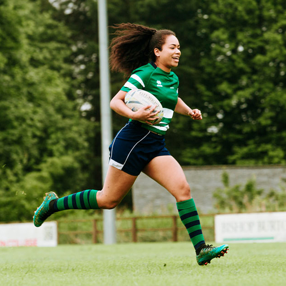 Female rugby player runs across pitch carrying ball whilst playing for the women's rugby academy at Bishop Burton College.