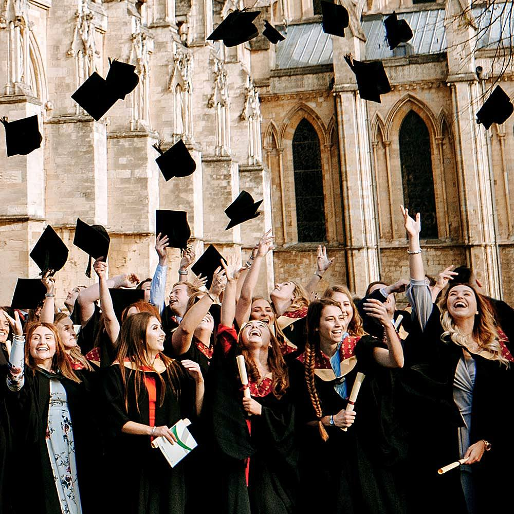 University Centre Bishop Burton degree students throwing caps outside Beverley Minster at graduation