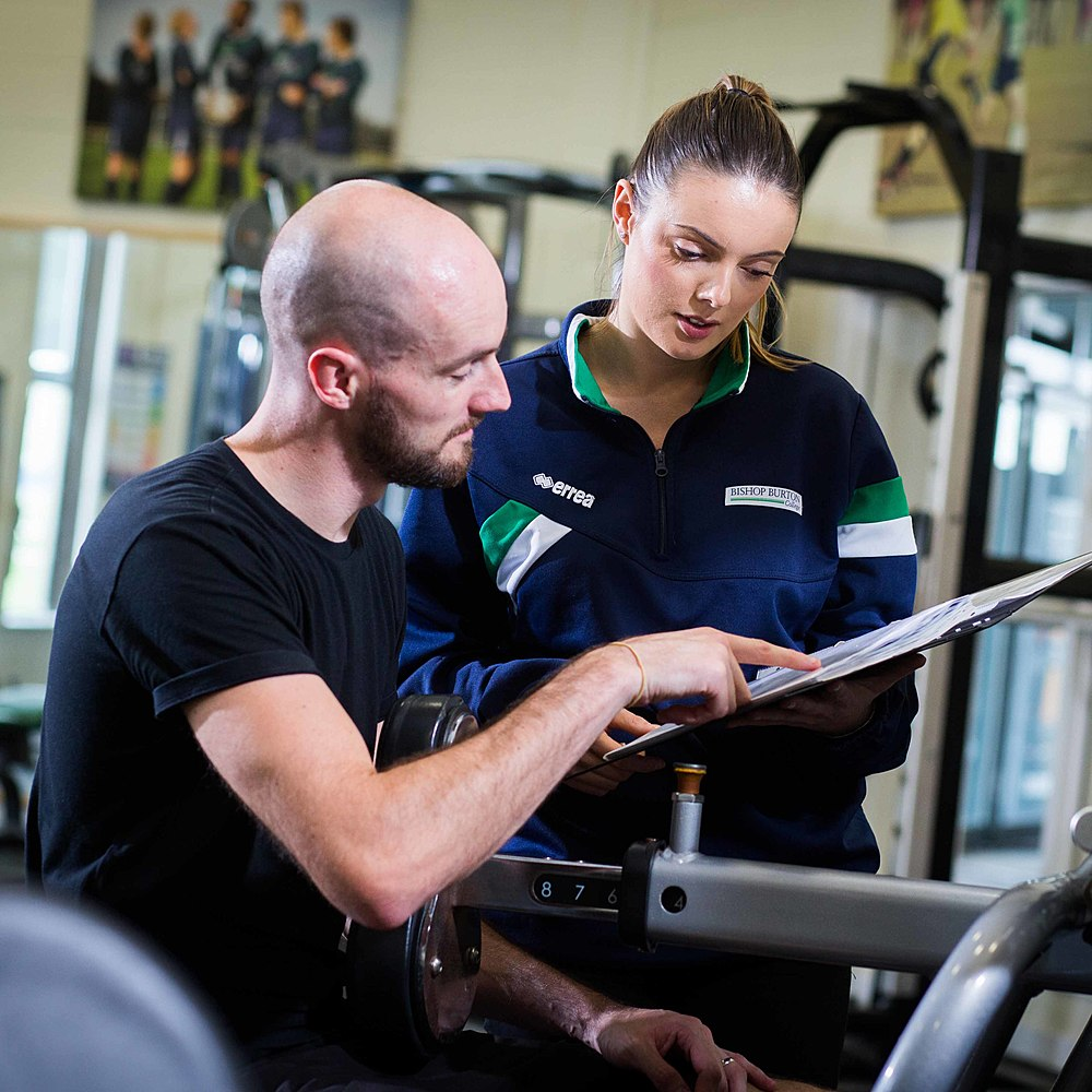 Gym instructor talks to training client sat on equipment at Bishop Burton College's Centre for Sport and Fitness
