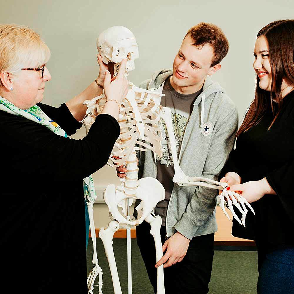 Health and Social Care students learning about the human body as a lecturer teaches with a skeleton at Bishop Burton College