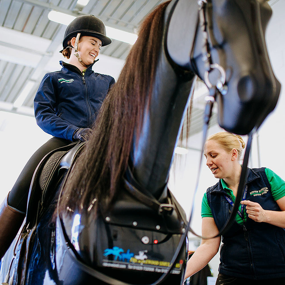 Equine academy rider on mechanical dressage horse being coached by University Centre Bishop Burton lecturer