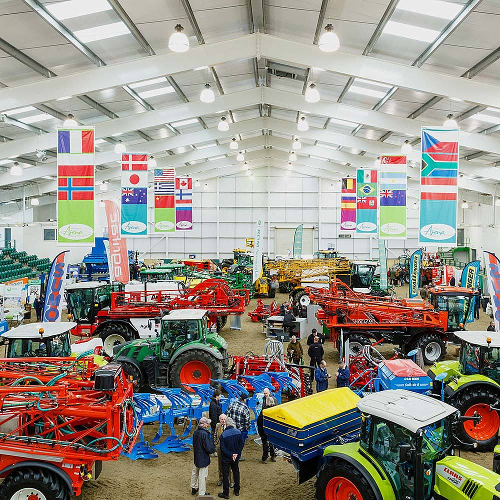 Large indoor equine arena full of machinery as part of the Agrii North farming conference at Bishop Burton College