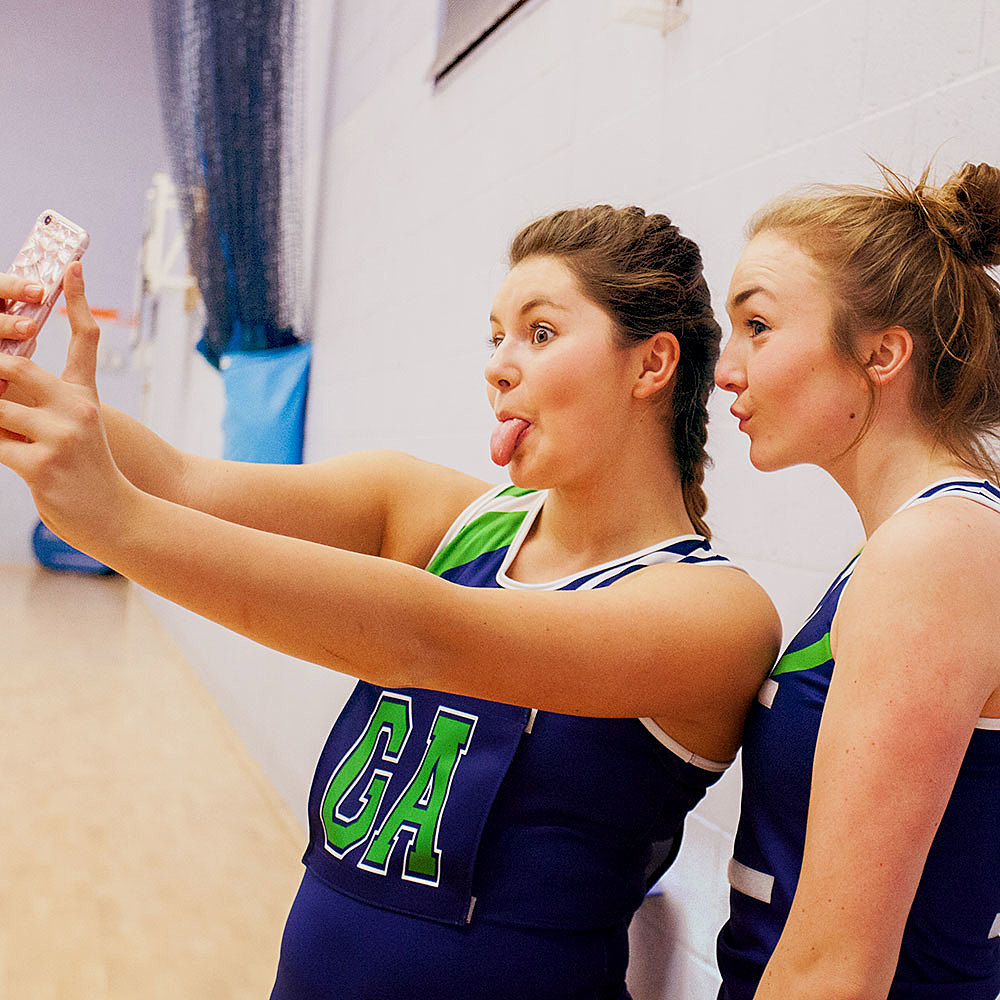 Netball academy players having fun whilst taking selfies in Bishop Burton College's sports hall
