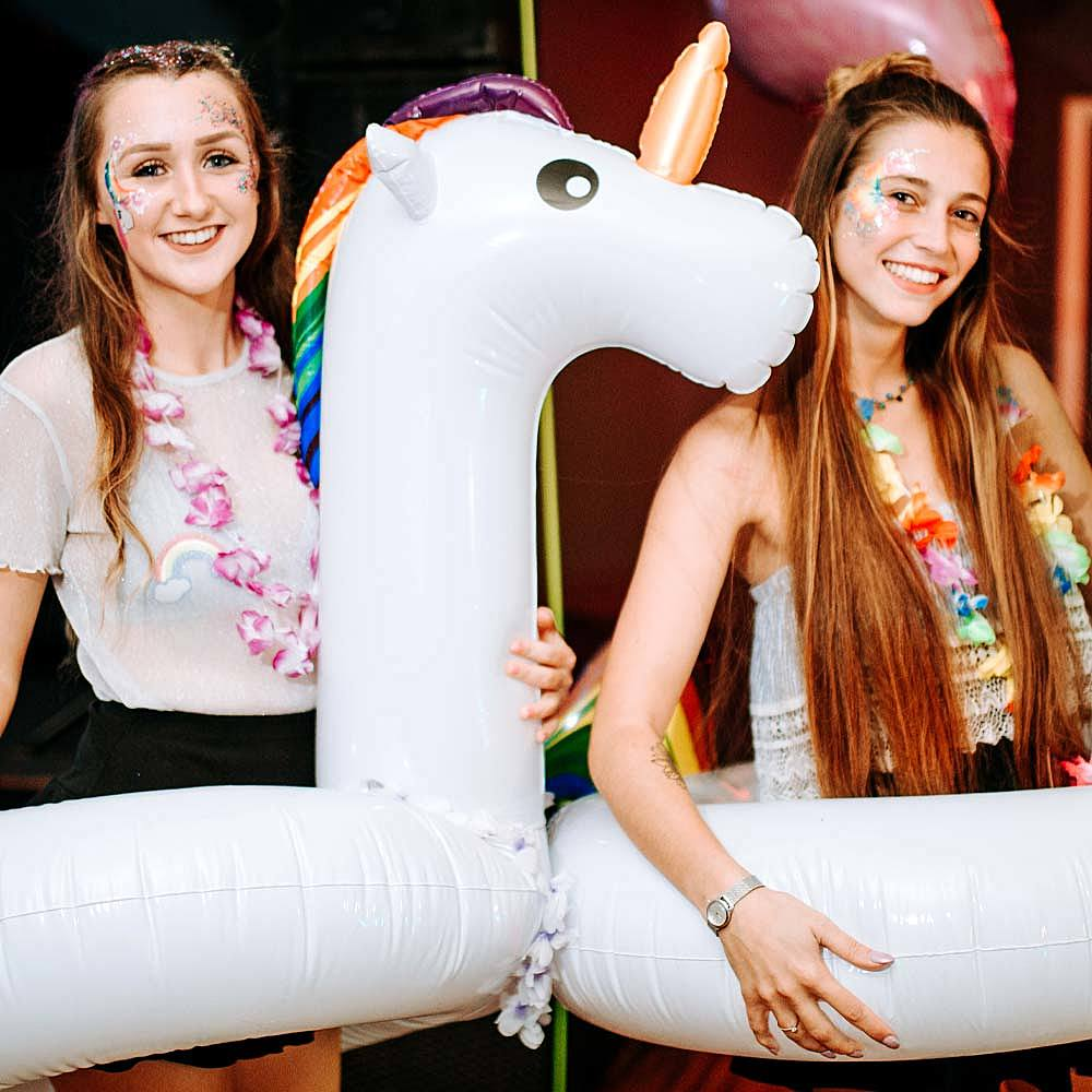 Degree students having fun in unicorn rubber rings at Hawaiian themed Freshers Week party at University Centre Bishop Burton